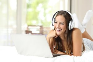 Girl with headphones reading in a laptop at home.jpg