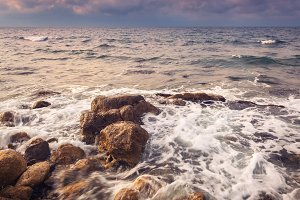Sea waves with rocks at sunset