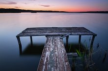 Wooden pier on lake at sunset