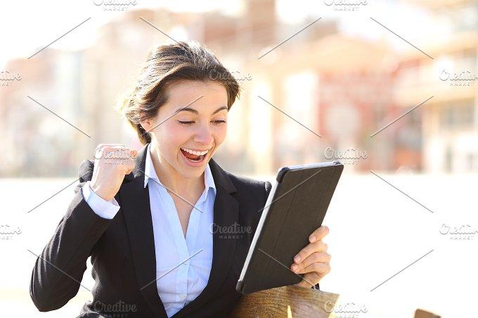 Euphoric successful executive watching a tablet.jpg - Business