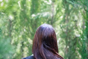 Woman back between trees