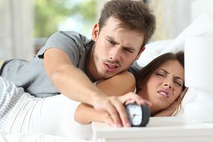 Angry couple turning off the alarm clock.jpg