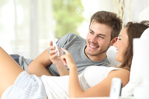 Couple sharing a smart phone on the bed.jpg
