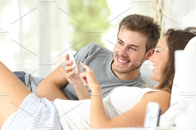 Couple sharing a smart phone on the bed.jpg - Technology