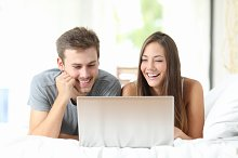 Couple watching videos on a laptop at home.jpg