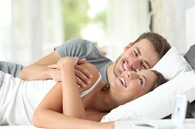 Couple flirting on a bed at home.jpg