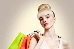 Portrait of beauty woman holding shopping bags, isolated