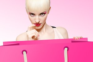 Fashion beauty portrait of woman with shopping bag on pink