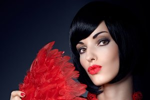 Fashion beauty portrait of brunette woman with red feather fan