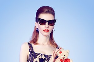 Beauty fashion redhead woman and loving teddy bear