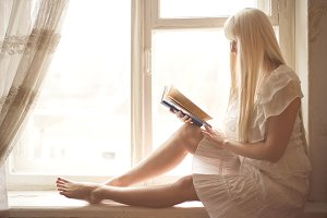 Blonde girl reading book