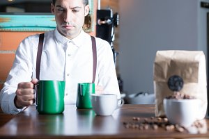 Barista and two pitchers on table