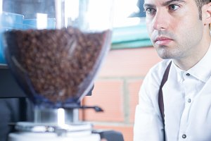 Close-up of bartender grinding coffe