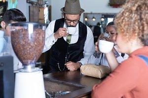 Four people degustate coffee
