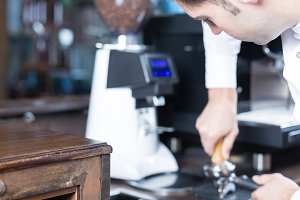 Male bartender pressing coffee