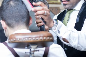 Stylish barber blow drying hair