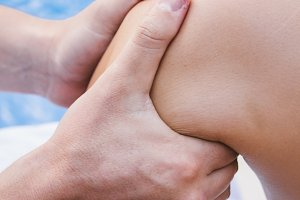 Hands of physiotherapist on a knee