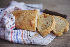 Fresh baked bread with seeds on rustic wooden background