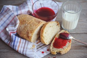 Freshly baked bread served with jam and glass of milk.