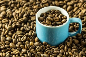 Coffee beans and blue coffee cup