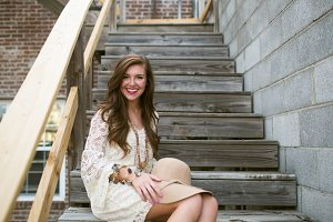 Brunette Smiling on Wooden Stairs
