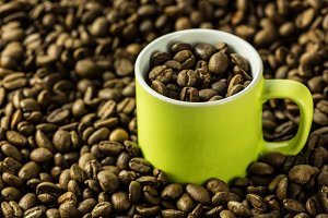 Coffee beans and green cup