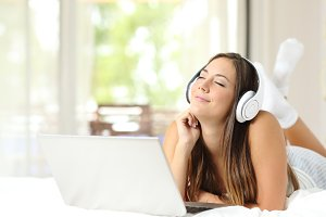 Girl listening music with headphones and laptop.jpg