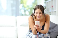 Girl listening music from smartphone at home.jpg