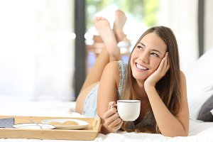 Happy girl having breakfast holding a coffee cup.jpg