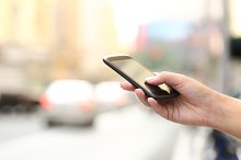 Woman hand texting on a smart phone in the street.jpg