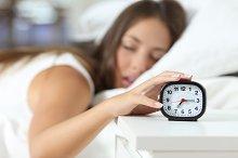 Wake up of an sleep girl stopping alarm clock.jpg