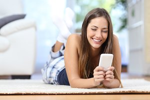 Teenager texting on the mobile phone in the living room.jpg