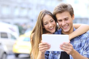 Happy couple sharing a tablet in the street.jpg