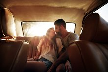 Romantic young couple in back seat