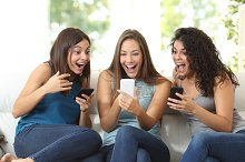 Three friends amazed watching a smart phone.jpg
