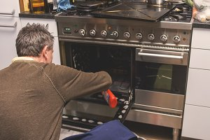 Man cleaning oven at home