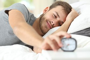Happy wake up of a happy man stopping alarm clock.jpg