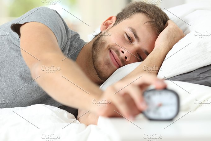 Happy wake up of a happy man stopping alarm clock.jpg - People