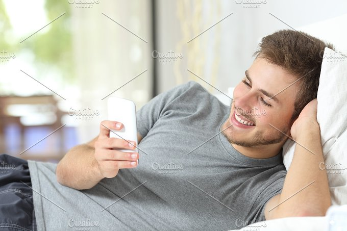Relaxed man using a smart phone at home.jpg - Technology