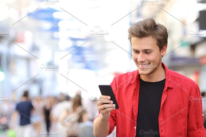 Man in red texting on a mobile phone.jpg - Technology
