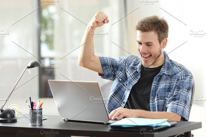 Euphoric winner man using a laptop at home.jpg - Technology