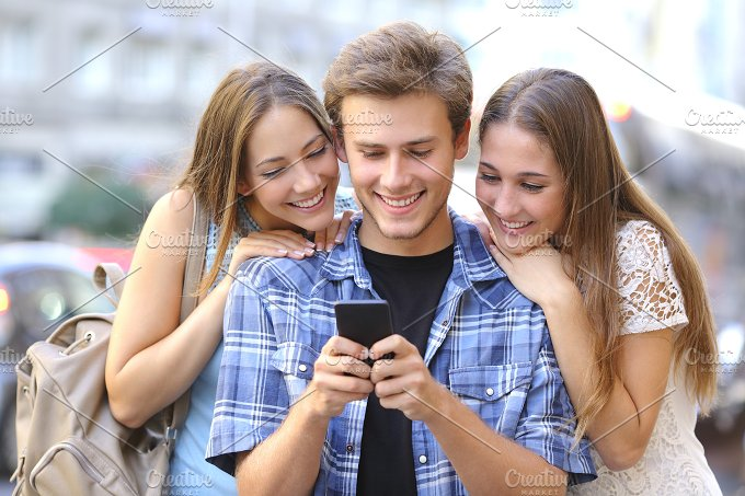 Friends sharing media in a smart phone.jpg - Technology