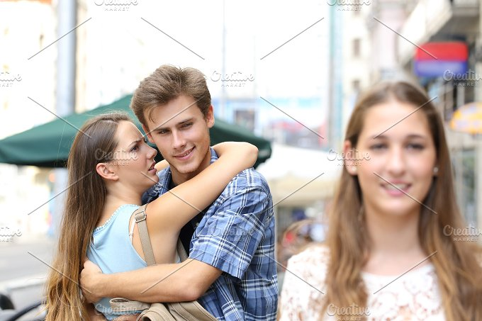 Unfaithful man hugging his girlfriend and looking another.jpg - People