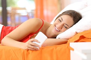 Teen using a smart phone in the bed.jpg