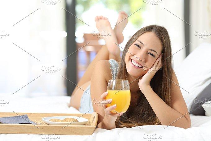 Happy girl having breakfast with orange juice.jpg - Food & Drink