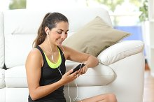 Fitness girl listening to music with earphones.jpg