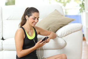 Fitness girl listening to music with earphones.jpg
