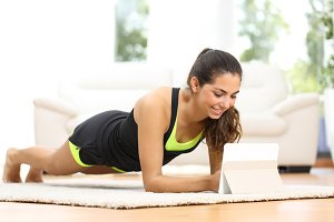 Fitness woman exercising watching fitness videos.jpg