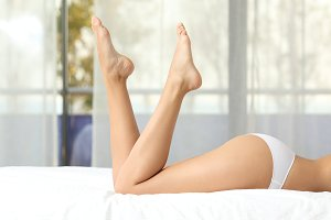 Perfect woman waxed legs on a bed.jpg