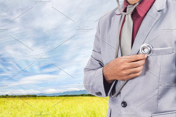 Man using stethoscope checking his heart on rice field background.jpg - Health